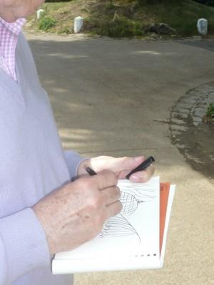 La main du dessinateur. Avec son feutre noir, Cabu croque l'une des serres d'Auteuil pour préparer un futur dessin. On peut retrouver ce fragment préparatoire dans le dessin présenté plus haut, sous le titre de cet article (photo d'Alain Marcel, mai 2012).
