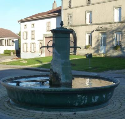 Doc. n° 2 Fontaine en fonte et pierre réalimentée dans un village de la plaine vosgienne. Au second plan, l'usoir est enherbé (cliché Jean-Pierre Husson, 2013).